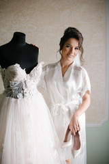 Happy smiling bride with beautiful hairstyle, make up in white robe standing near the mannequin with wedding dress in the morning. Woman preparing.