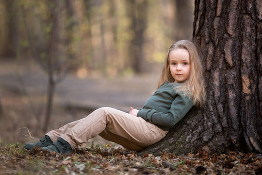 Girl is sitting under the tree in the park