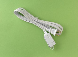New white extension cord on a green paper background.