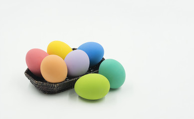 colorful easter eggs in wood basket on isolate background