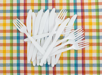 Plastic white picnic forks and knives on a tablecloth.