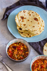 Tortillas with chili con carne. Grey background blue and grey bowls, plates.