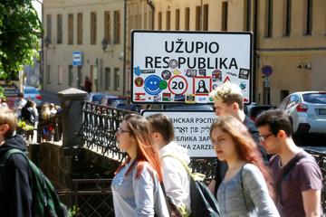 People walk past a sign of the Uzupis neighbourhood in Vilnius