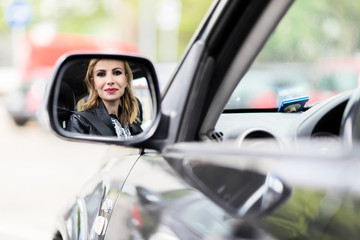Young lady driving her car reflected in a mirror