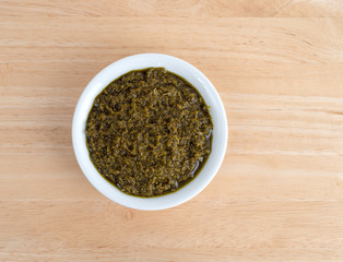 Top view of a bowl of chopped parsley in canola oil on a wood table.