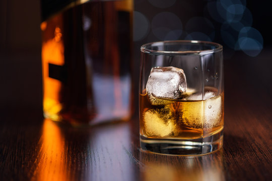 a glass of whiskey on the rocks and a bottle on the table.