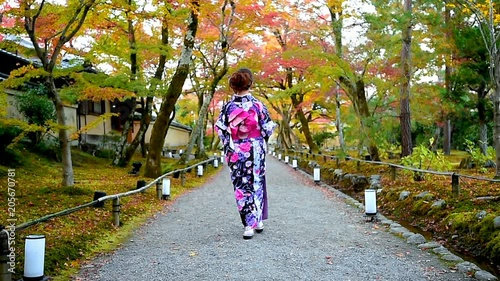 Wall mural Asian woman wearing japanese traditional kimono walking in autumn park, Kyoto in Japan.