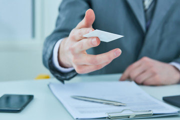 Businessman in suit offering plastic credit card. Credit and banking account concept.