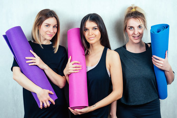 three attractive and young female girlfriends hold a roll yoga mat and do selfie on the phone