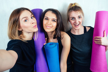 three attractive and young female girlfriends hold a roll yoga mat and do selfie on the phone. concept of yoga practice and female friendship