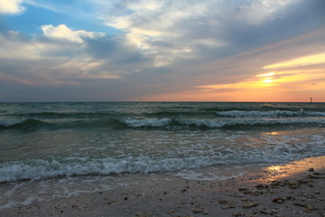 Pastel sunset sky with low clouds over the horizon with green waters from the ocean with waves crashing into the beach shoreline