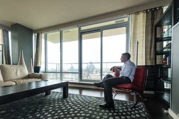 Business Man in High Rise Condo on Phone