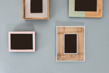 Multiple many blank small picture frames on colorful wall