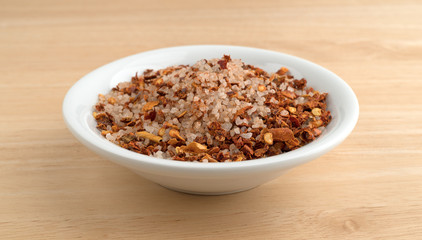 Greek spice rub in a white bowl atop a wood table.