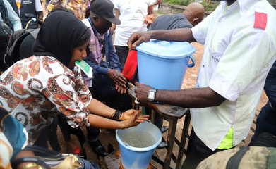 A Congolese health worker instructs residents about washing their hands as a preventive measure against Ebola in Mbandaka