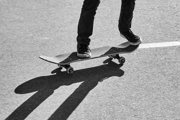 Shadow of a skateboarder on asphalt. Black and white image
