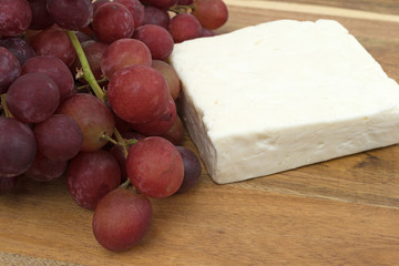 Block of feta cheese with fresh grapes on a wood cutting board.
