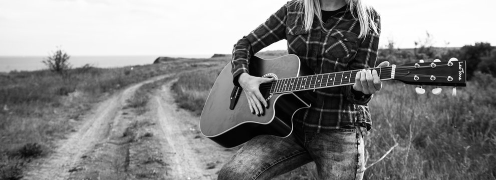 the girl on the road in the desert with the guitar in her hands looks into the distance