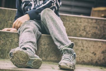 Löchrige Schuhe als Symbol für eine Kindheit in sozialer Benachteiligung
