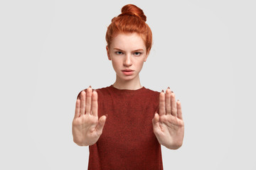 Leave me in peace, please! Don`t bother! Angry red haired female pulls palms at camera, shows stop gesture, wears casual clothing, isolated on white background. Freckled student rejects answering