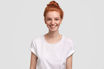 Waist up portrait of delighted freckled redhead woman with pleasant smile, wears casual white t shirt, rejoices good news, isolated over studio background. Foxy female teenager spends time with friend