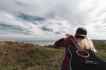 girl with a guitar on a cliff near the ocean