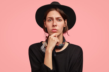 Portrait of good looking female adult wears stylish black cowboy`s hat, holds chin and looks confidently at camera, thinks about new horse racing and want to organise competition, stands indoor
