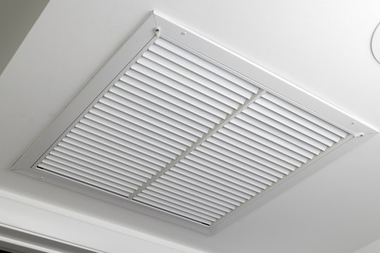 White Ceiling Air Filter Vent Grid One large white painted metal furnace air vent grill with many openings on a ceiling close-up. Square outflow air filter door vent in a modern home ceiling