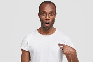 Portrait of stunned attractive young male looks with bated breath, indicates at blank copy space of white tshirt, shows place for your logo or advertisement, poses against studio concrete wall