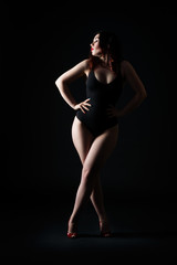 Beautiful sexy woman in bodysuit posing on black background, low key studio shot