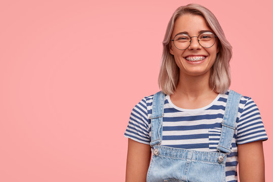 Charming pleasant looking female in stylish denim dungaree and spectacles, listens carefully to somebody`s point of view, expresses positiveness, stands against pink background with copy space