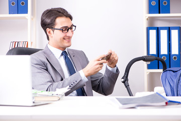 Businessman looking after newborn baby in office