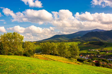 beautiful landscape in mountains. trees on the grassy hills of the Volovets serpentine. village at the foot of the mountain. lovely cloud formation over the ridge on a sunny afternoon