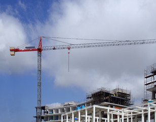 tall red crane on a large construction site with metal framework scaffolding blue sky and clouds