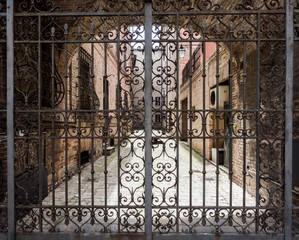 Hand-worked wrought iron gate with internal courtyard of an old Italian palace.
