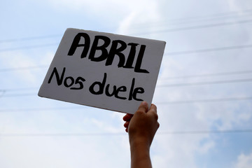 """A demonstrator holds up a sign that reads """"April hurts us"""" during protest against Nicaraguan President Daniel Ortega's government in Managua"""