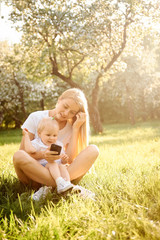 Young beautiful mother is playing with her child in the summer in the park in the spring and making selfie on the phone. The concept of a family and a healthy lifestyle