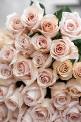 pastel pink roses. Bouquet of beautiful flowers on wooden table. Floristry concept. the work of the florist at a flower shop. Vertical photo