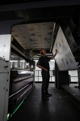 Team Manager Nick Taylor looks at copies of The Times newspaper as the first copies of the Royal Wedding edition come off the presses at the News UK printing presses at Broxbourne in Hertfordshire