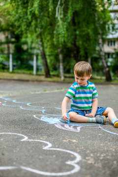 Cute boy and girl drawing with chalk on the sidewalk in the park.