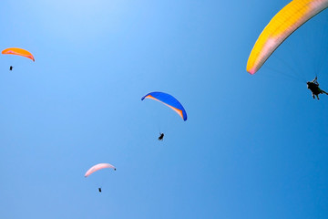 paroplane group flying against the blue sky..Above the Mediterranean Sea, Israel..Extreme sports, enjoy life, appreciate the time,.tandem paragliding, controlled pilot
