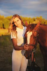 A woman jockey strokes a horse after a horse race.
