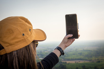 Woman enjoying in nature and taking picture in the mountain with mobile phone.