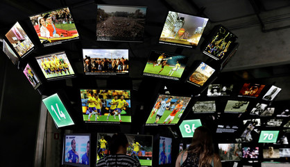Visitors look at panels on soccer moments at the Football Museum in Sao Paulo