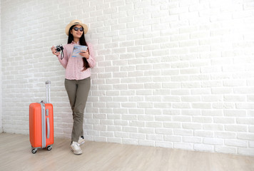 Young asian woman traveler with luggage holding vintage camera and map standing in white room with copy space, people summer holiday vacation