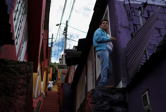 A woman smokes a cigarette at the entrance of her house on the side of a hill in the Los Puentes neighbourhood in Bogota