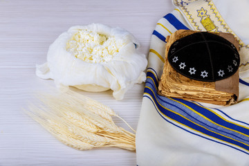 Cheese and Shofar, dairy products on wooden white background. Jewish holiday Shavuot concept. View from above