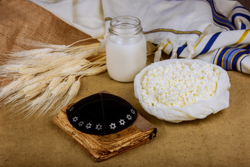 imDairy products and on wheat field table. torah, Symbols of jewish holiday - Shavuot