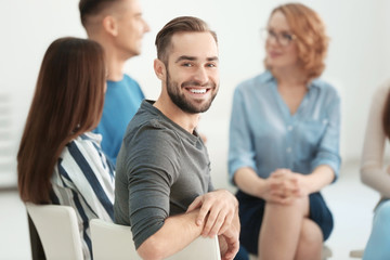 Handsome man at group psychotherapy session indoors
