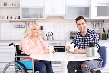 Young man and mature woman in wheelchair drinking tea indoors